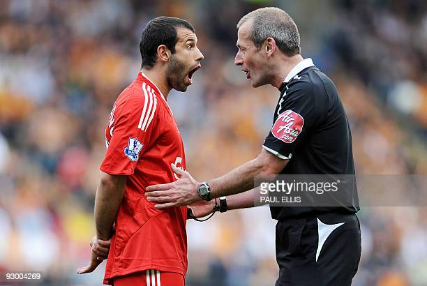 Liverpool's Argentinian midfielder Javier Mascherano is spoken to by referee Martin Atkinson during the English Premier League football match between...