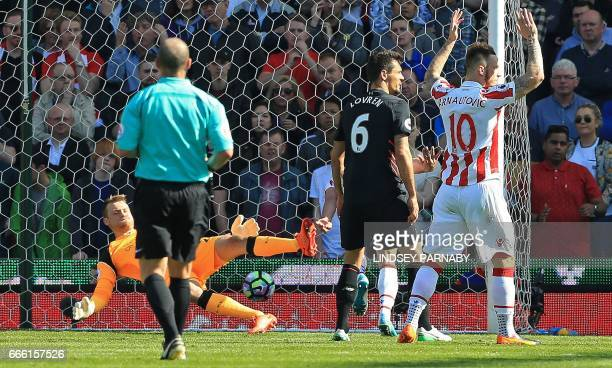Liverpool's Belgian goalkeeper Simon Mignolet dives but fails to save a shot from Stoke City's Englishborn Irish striker Jonathan Walters leading to...