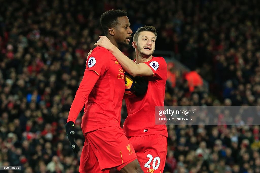 Liverpool's Belgian striker Divock Origi (L) celebrates scoring their second goal to equalise with Liverpool's English midfielder Adam Lallana (R) during the English Premier League football match between Liverpool and West Ham United at Anfield in Liverpool, north west England on December 11, 2016. / AFP / Lindsey PARNABY / RESTRICTED TO EDITORIAL USE. No use with unauthorized audio, video, data, fixture lists, club/league logos or 'live' services. Online in-match use limited to 75 images, no video emulation. No use in betting, games or single club/league/player publications. /