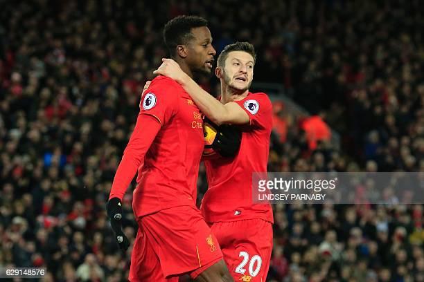 Liverpool's Belgian striker Divock Origi celebrates scoring their second goal to equalise with Liverpool's English midfielder Adam Lallana during the...