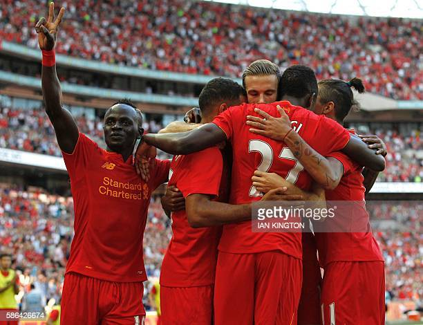 Liverpool's Belgian striker Divock Origi celebrates with teammates after scoring their third goal during the preseason International Champions Cup...