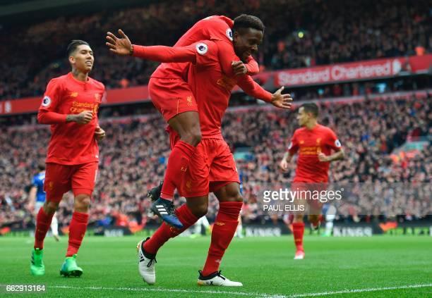 Liverpool's Belgian striker Divock Origi celebrates with teammates after scoring their third goal during the English Premier League football match...