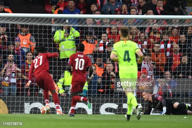 Liverpool's Belgian striker Divock Origi shoots and scores during the UEFA Champions league semi-final second leg football match between Liverpool...