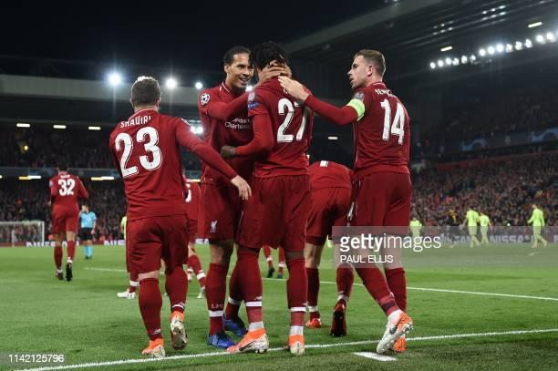 Liverpool's Belgium striker Divock Origi celebrates with Liverpool's Dutch defender Virgil van Dijk after scoring their fourth and winning goal...