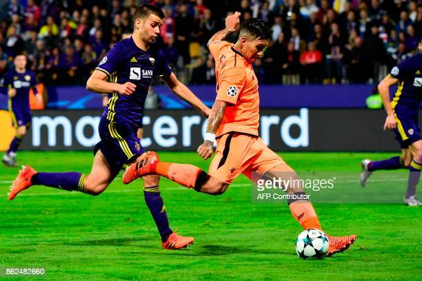 Liverpool's Brazilian forward Roberto Firmino runs with the ball as Maribor's Slovenian defender Mitja Viler attempts to stop him during the UEFA...
