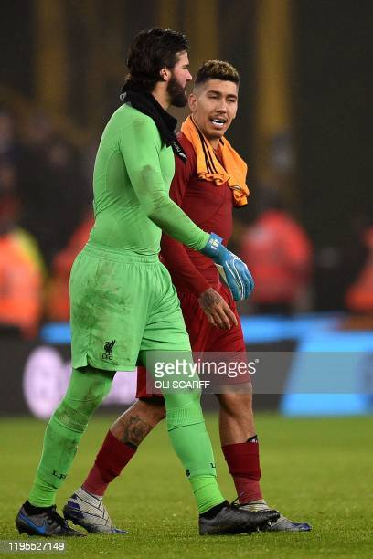 Liverpool's Brazilian goalkeeper Alisson Becker and Liverpool's Brazilian midfielder Roberto Firmino react at the final whistle during the English...