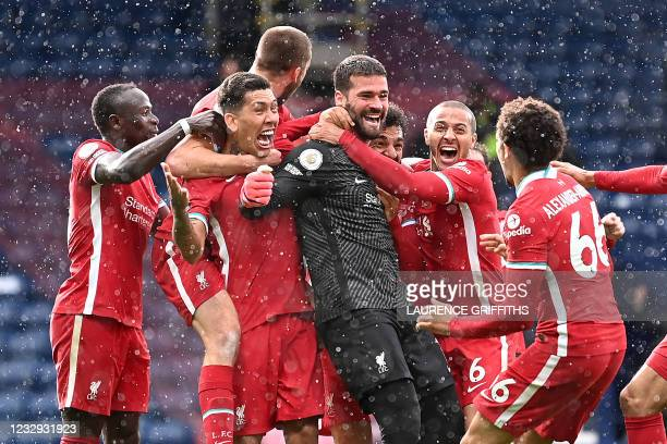 Liverpool's Brazilian goalkeeper Alisson Becker celebrates scoring his team's second goal with his teammates during the English Premier League...