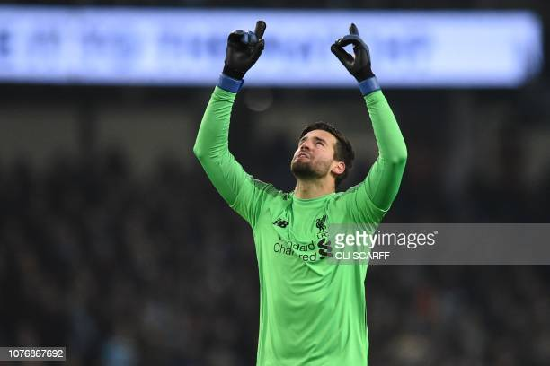 Liverpool's Brazilian goalkeeper Alisson Becker celebrates their first goal during the English Premier League football match between Manchester City...