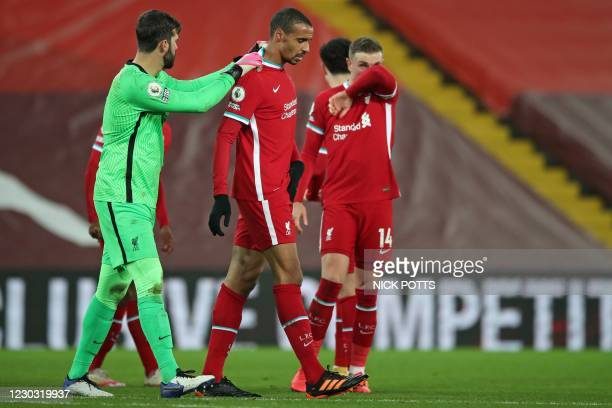Liverpool's Brazilian goalkeeper Alisson Becker consoles Liverpool's German-born Cameroonian defender Joel Matip as he leaves the game after picking...