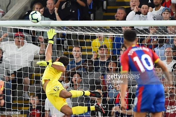 Liverpool's Brazilian goalkeeper Alisson Becker dives as Crystal Palace's English midfielder Andros Townsend watches his shot hit the crossbar during...