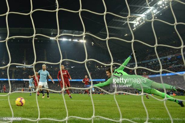 Liverpool's Brazilian goalkeeper Alisson Becker dives but cannot prevent the winning goal from Manchester City's German midfielder Leroy Sane during...