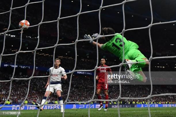 TOPSHOT Liverpool's Brazilian goalkeeper Alisson Becker dives for the ball in front of Tottenham Hotspur's Belgian defender Jan Vertonghen and...