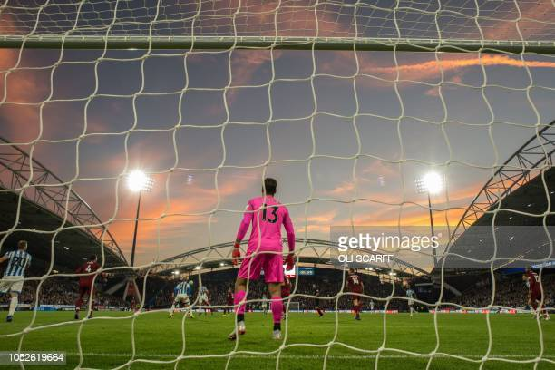 Liverpool's Brazilian goalkeeper Alisson Becker guards his goalmouth as the sky turns pink as the sun sets over the John Smith's stadium during the...
