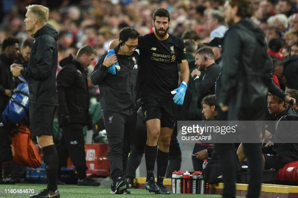 Liverpool's Brazilian goalkeeper Alisson Becker is assisted off the field with an injury during the English Premier League football match between...
