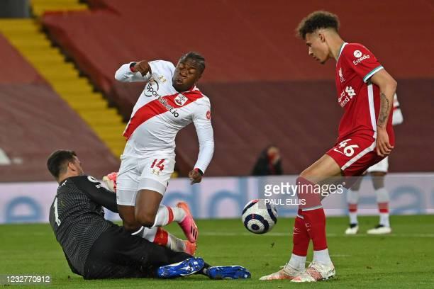 Liverpool's Brazilian goalkeeper Alisson Becker makes a save at the feet of Southampton's Irish-born striker Michael Obafemi during the English...