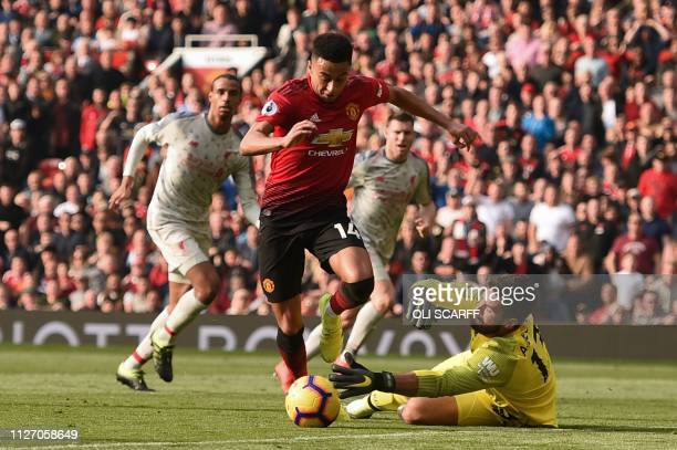 Liverpool's Brazilian goalkeeper Alisson Becker makes a save from Manchester United's English midfielder Jesse Lingard during the English Premier...