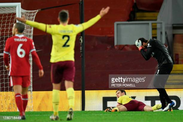 Liverpool's Brazilian goalkeeper Alisson Becker reacts after conceding a penalty by fouling Burnley's English striker Ashley Barnes during the...