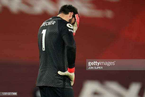 Liverpool's Brazilian goalkeeper Alisson Becker reacts after conceding their third goal during the English Premier League football match between...