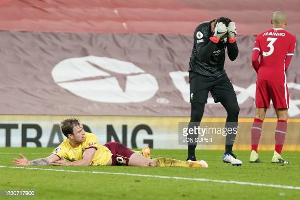 Liverpool's Brazilian goalkeeper Alisson Becker reacts after fouling Burnley's English striker Ashley Barnes to concede a penalty during the English...