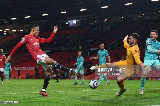 Liverpool's Brazilian goalkeeper Alisson Becker spreads himself to save a shot from Manchester United's English striker Mason Greenwood during the...