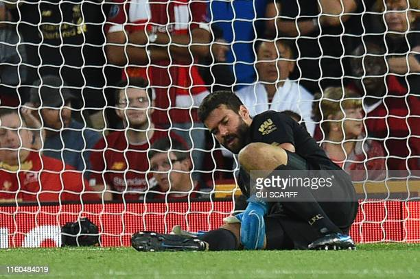 Liverpool's Brazilian goalkeeper Alisson Becker waits to receive medical attention during the English Premier League football match between Liverpool...