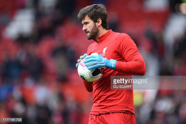 Liverpool's Brazilian goalkeeper Alisson Becker warms up ahead of the English Premier League football match between Manchester United and Liverpool...