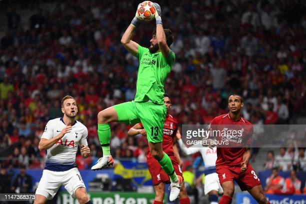 Liverpool's Brazilian goalkeeper Alisson makes a save as Tottenham Hotspur's English forward Harry Kane approaches during the UEFA Champions League...