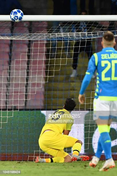 Liverpool's Brazilian goalkeeper Alisson watches the ball hit the crossbar following a shot by Napoli's Belgian forward Dries Mertens during the UEFA...