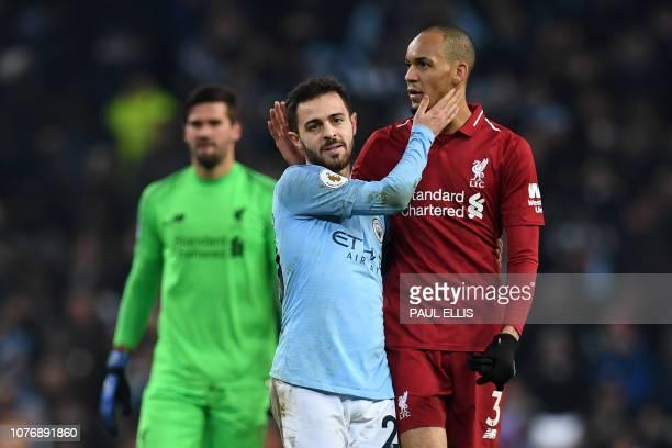 Liverpool's Brazilian midfielder Fabinho and Manchester City's Portuguese midfielder Bernardo Silva embrace on the pitch after the English Premier...