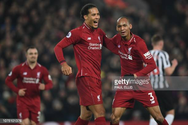 Liverpool's Brazilian midfielder Fabinho celebrates with Liverpool's Dutch defender Virgil van Dijk after scoring their fourth goal during the...