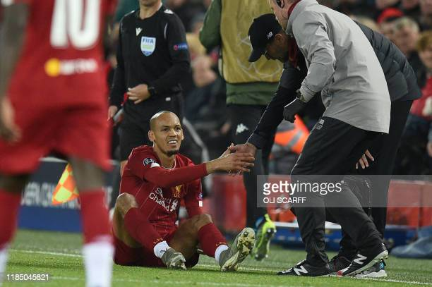 Liverpool's Brazilian midfielder Fabinho is greeted by Liverpool's German manager Jurgen Klopp as he prepares to leave the pitch injured during the...
