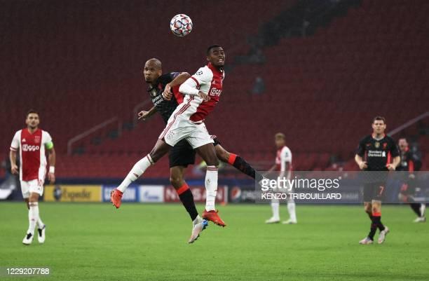 Liverpool's Brazilian midfielder Fabinho jumps for the ball with Ajax's Dutch midfielder Ryan Gravenberch during the UEFA Champions League Group D...
