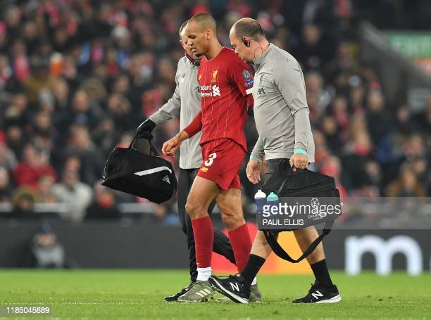 Liverpool's Brazilian midfielder Fabinho leaves the pitch injured during the UEFA Champions league Group E football match between Liverpool and...