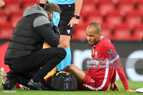 Liverpool's Brazilian midfielder Fabinho receives medical attention after picking up an injury during the UEFA Champions league Group D football...