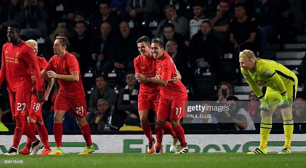 Liverpool's Brazilian midfielder Philippe Coutinho (centre L) celebrates after scoring their second goal with teammate Roberto Firmino as Derby's English goalkeeper Jonathan Mitchell (R) looks on during the English League Cup third-round football match between Derby County and Liverpool at iPro Stadium in Derby, central England on September 20, 2016. / AFP / PAUL ELLIS / RESTRICTED TO EDITORIAL USE. No use with unauthorized audio, video, data, fixture lists, club/league logos or 'live' services. Online in-match use limited to 75 images, no video emulation. No use in betting, games or single club/league/player publications. /