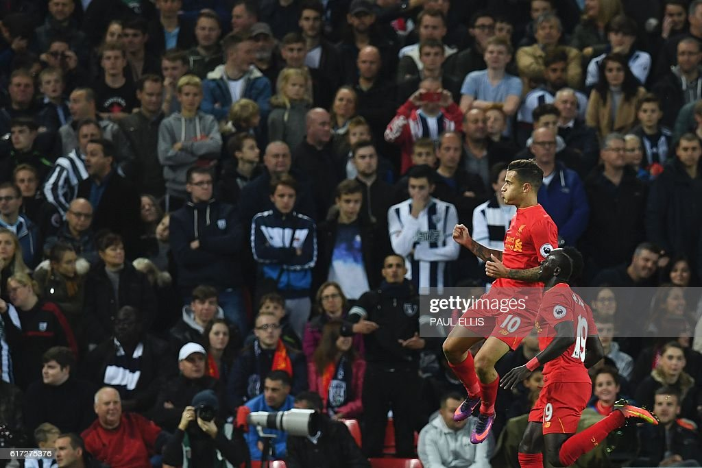 Liverpool's Brazilian midfielder Philippe Coutinho (L) celebrates scoring their second goal with Liverpool's Senegalese midfielder Sadio Mane (R) during the English Premier League football match between Liverpool and West Bromwich Albion at Anfield in Liverpool, north west England on October 22, 2016. / AFP / PAUL ELLIS / RESTRICTED TO EDITORIAL USE. No use with unauthorized audio, video, data, fixture lists, club/league logos or 'live' services. Online in-match use limited to 75 images, no video emulation. No use in betting, games or single club/league/player publications. /