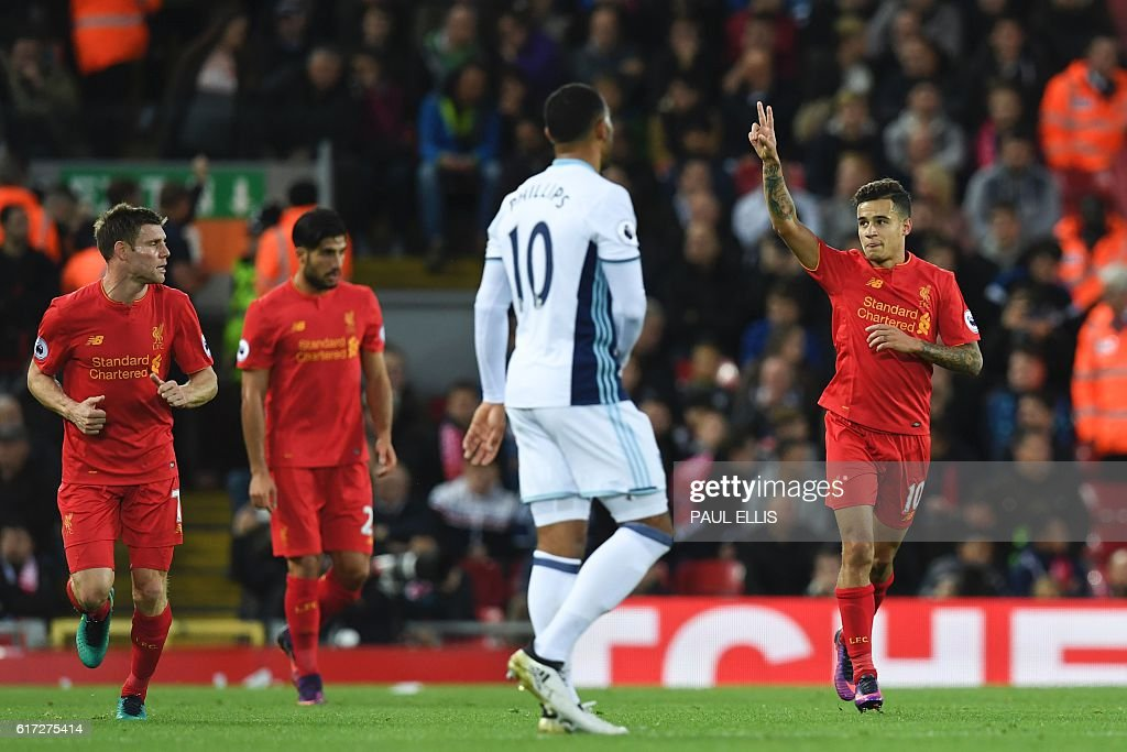 Liverpool's Brazilian midfielder Philippe Coutinho (R) celebrates scoring their second goal during the English Premier League football match between Liverpool and West Bromwich Albion at Anfield in Liverpool, north west England on October 22, 2016. / AFP / PAUL ELLIS / RESTRICTED TO EDITORIAL USE. No use with unauthorized audio, video, data, fixture lists, club/league logos or 'live' services. Online in-match use limited to 75 images, no video emulation. No use in betting, games or single club/league/player publications. /