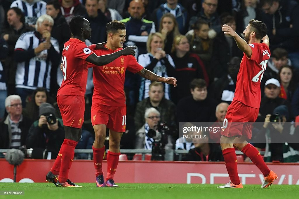 Liverpool's Brazilian midfielder Philippe Coutinho (C) celebrates scoring their second goal with Liverpool's Senegalese midfielder Sadio Mane (L) and Liverpool's English midfielder Adam Lallana (R) during the English Premier League football match between Liverpool and West Bromwich Albion at Anfield in Liverpool, north west England on October 22, 2016. / AFP / PAUL ELLIS / RESTRICTED TO EDITORIAL USE. No use with unauthorized audio, video, data, fixture lists, club/league logos or 'live' services. Online in-match use limited to 75 images, no video emulation. No use in betting, games or single club/league/player publications. /