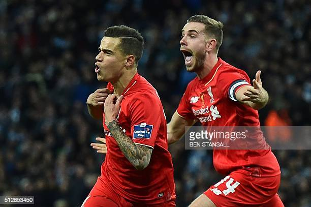 Liverpool's Brazilian midfielder Philippe Coutinho celebrates with Liverpool's English midfielder Jordan Henderson after scoring their first goal to...