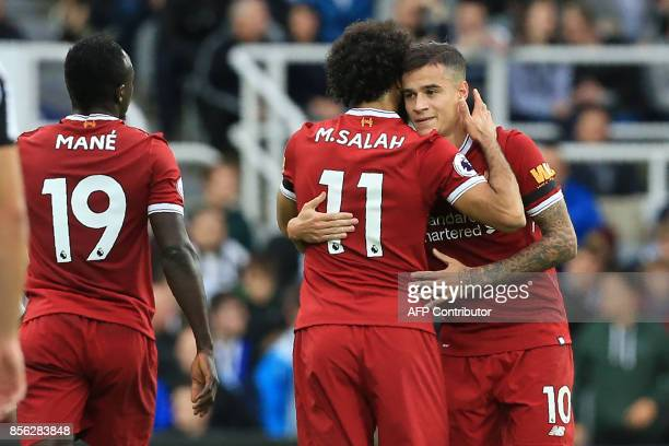 Liverpool's Brazilian midfielder Philippe Coutinho celebrates with Liverpool's Egyptian midfielder Mohamed Salah after scoring the opening goal of...