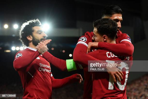 Liverpool's Brazilian midfielder Philippe Coutinho is hugged by Liverpool's German midfielder Emre Can and Liverpool's Egyptian midfielder Mohamed...
