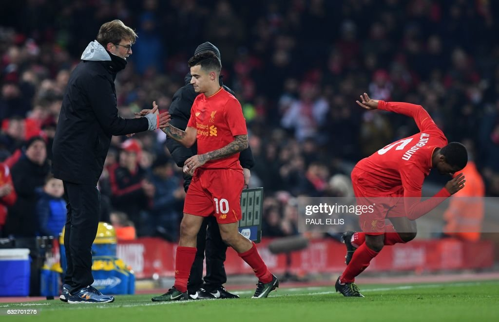 Liverpool's Brazilian midfielder Philippe Coutinho (C) shakes hands with Liverpool's German manager Jurgen Klopp after being substituted off for Liverpool's Dutch midfielder Georginio Wijnaldum during the EFL (English Football League) Cup semi-final second-leg football match between Liverpool and Southampton at Anfield in Liverpool, north west England on January 25, 2017. / AFP PHOTO / Paul ELLIS / RESTRICTED TO EDITORIAL USE. No use with unauthorized audio, video, data, fixture lists, club/league logos or 'live' services. Online in-match use limited to 75 images, no video emulation. No use in betting, games or single club/league/player publications. /