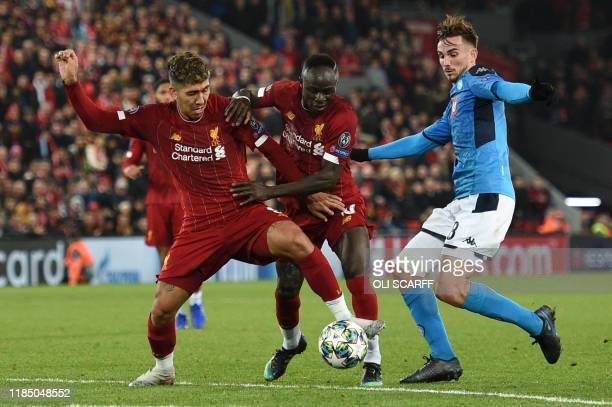 Liverpool's Brazilian midfielder Roberto Firmino and Liverpool's Senegalese striker Sadio Mane clash as they vie with Napoli's Spanish defender...