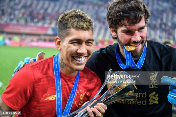 Liverpool's Brazilian midfielder Roberto Firmino and Liverpool's Brazilian goalkeeper Alisson Becker pose with the trophy following the 2019 FIFA...