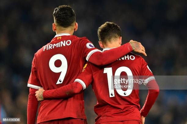 Liverpool's Brazilian midfielder Roberto Firmino and Liverpool's Brazilian midfielder Philippe Coutinho walk with arms around each other during the...