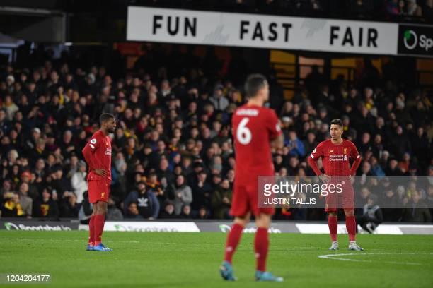 Liverpool's Brazilian midfielder Roberto Firmino and teammates react after Watford's Senegalese midfielder Ismaila Sarr scores his team's second goal...