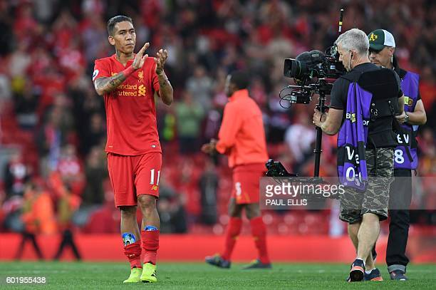 Liverpool's Brazilian midfielder Roberto Firmino applauds on the pitch after the English Premier League football match between Liverpool and...