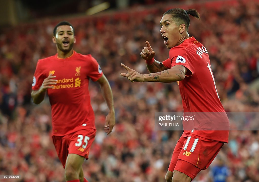 Liverpool's Brazilian midfielder Roberto Firmino (R) celebrates after scoring their fourth goal during the English Premier League football match between Liverpool and Leicester City at Anfield in Liverpool, north west England on September 10, 2016. / AFP / Paul ELLIS / RESTRICTED TO EDITORIAL USE. No use with unauthorized audio, video, data, fixture lists, club/league logos or 'live' services. Online in-match use limited to 75 images, no video emulation. No use in betting, games or single club/league/player publications. /