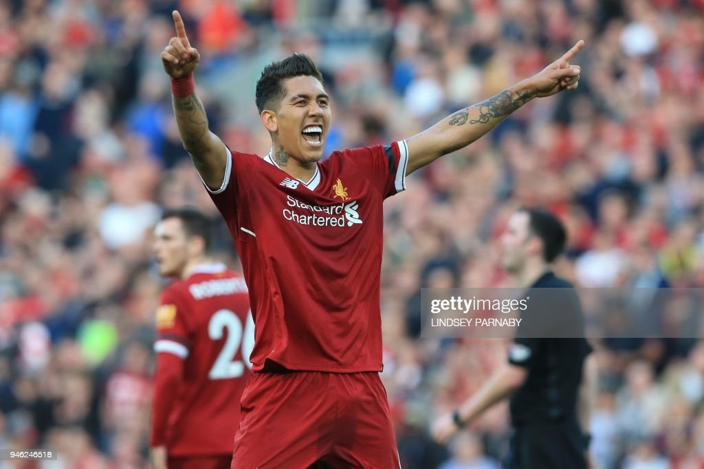 Liverpool's Brazilian midfielder Roberto Firmino celebrates after scoring their third goal during the English Premier League football match between Liverpool and Bournemouth at Anfield in Liverpool, north west England on April 14, 2018. / AFP PHOTO / Lindsey PARNABY / RESTRICTED TO EDITORIAL USE. No use with unauthorized audio, video, data, fixture lists, club/league logos or 'live' services. Online in-match use limited to 75 images, no video emulation. No use in betting, games or single club/league/player publications. /