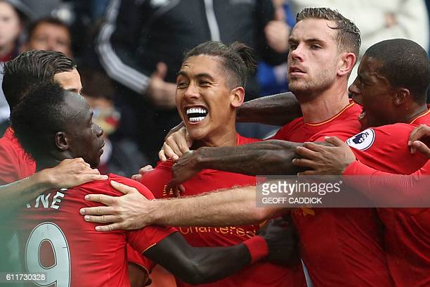 Liverpool's Brazilian midfielder Roberto Firmino celebrates scoring their first goal to equalise 1-1 during the English Premier League football match...